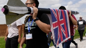 Project Imua students carrying their rocket with the Hawaii flag