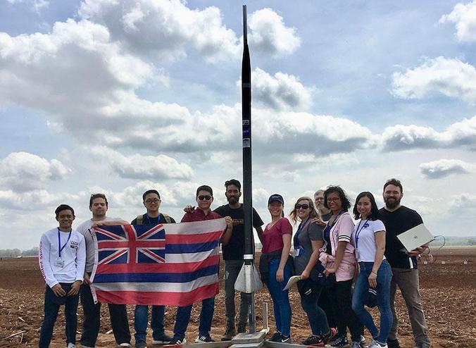Team posing with rocket and Hawaii flag