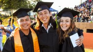 three students in graduation regalia