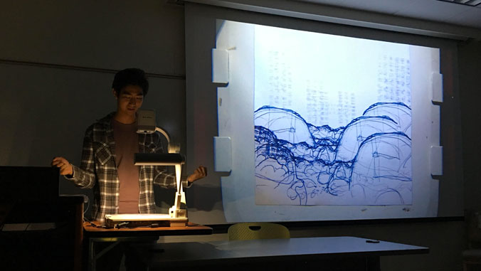 Student presents drawing in darkened classroom.