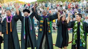 students in graduation regalia holding hands