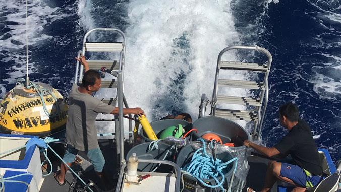 PacIOOS crew redeplay a wave buoy to sea.