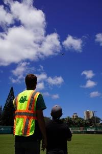 Man instructs boy operating drone