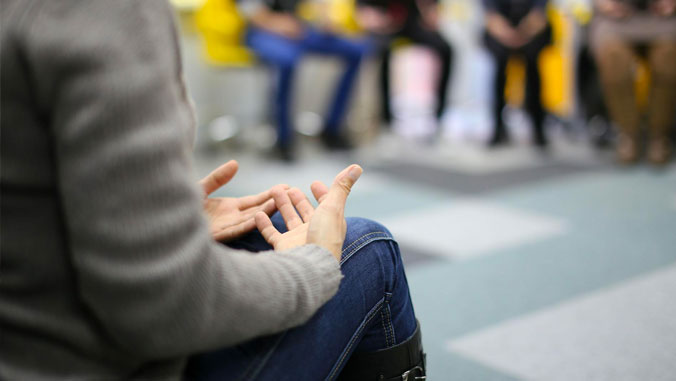 An unidentified person's hands in a circle discussion