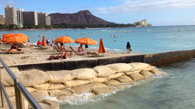 Sunbathers on Waikīkī Beach with sand bags piled up