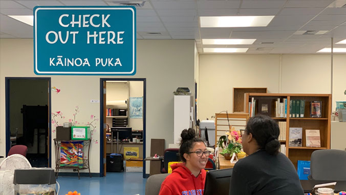 Two students talking in U H Maui College's library with a sign that says Check Out Here and the words in Hawaiian