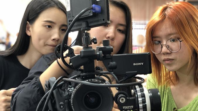 3 students setting up film camera