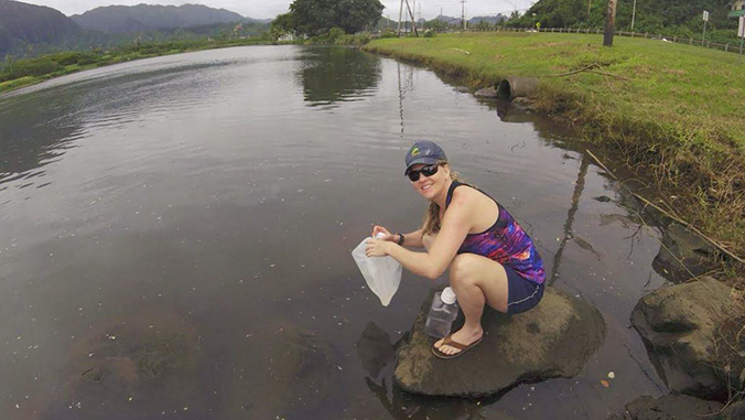 Student collecting water samples in the field