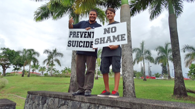 U H Hilo people holding signs