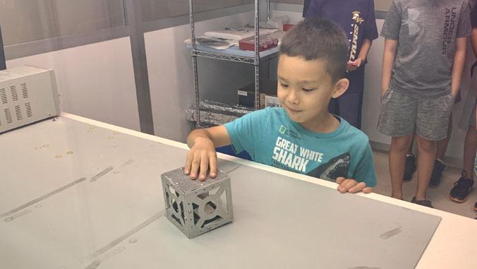 boy touching cube
