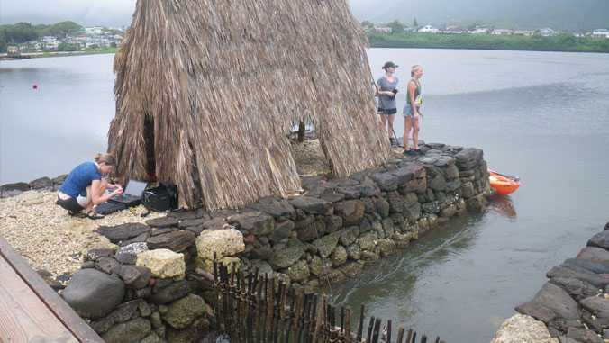 Three students outside a thatched hut