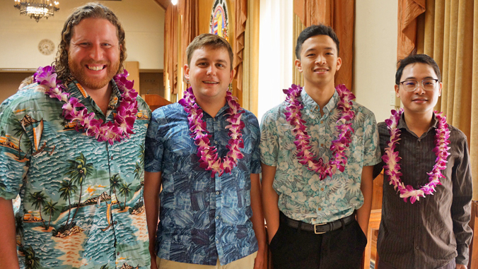 four people standing in Honolulu City Coucil wearing lei