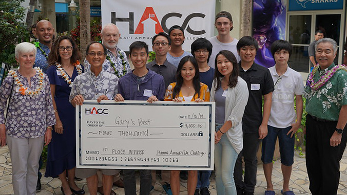 Winning team holding a check with Governor Ige