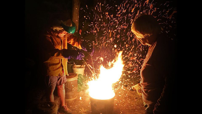 people lighting a pottery piece in a fire