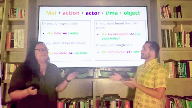 two presenters in front of screen