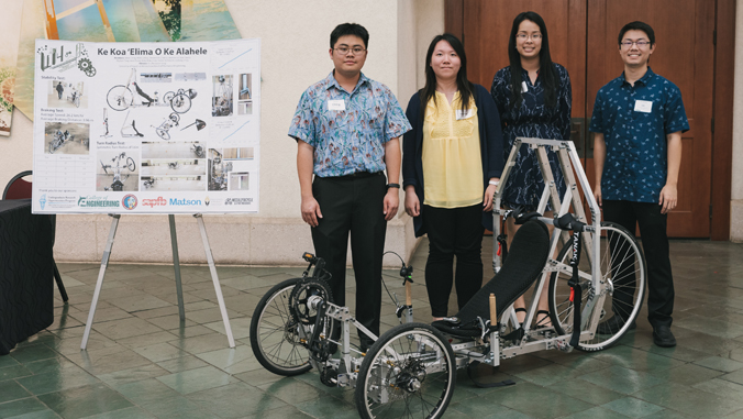 four engineering students standing in front of project