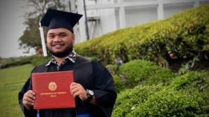 U H Hilo graduate holding diploma