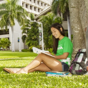student sitting under a tree studying