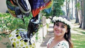 U H West Oahu graduate holding balloons