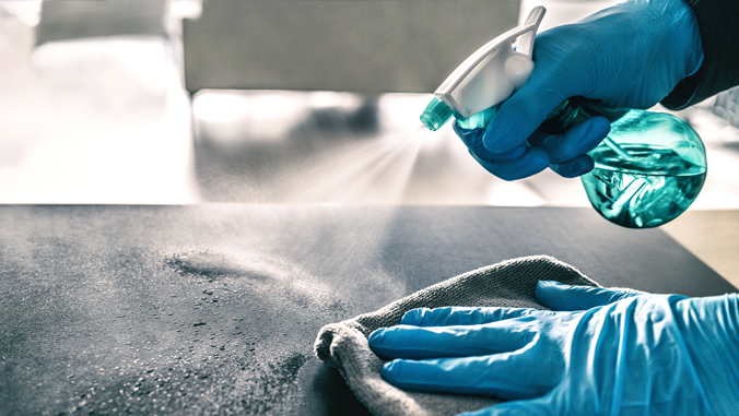 hands spraying and cleaning a desk