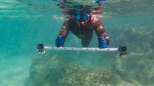 man swimming with go pros
