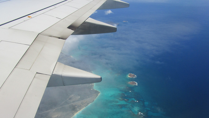 Airplane wing over the ocean