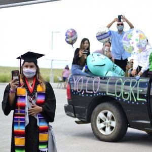 student graduate with family behind in car