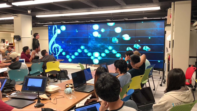 students sitting around a table looking at a large screen