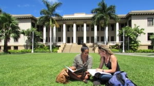 two people sitting down on grass looking at a book