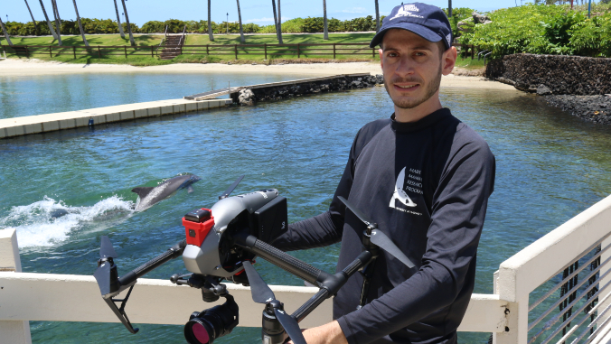 man holding drone with dolphin in background