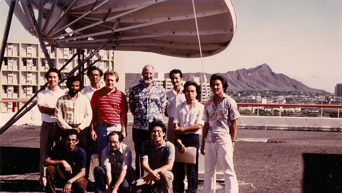 people standing next to a satellite with Diamond Head in the background