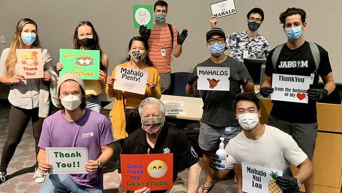 JABSOM students with masks holding up signs