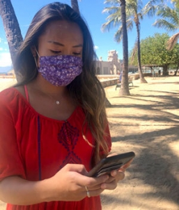 girl wearing mask mask looking at phone