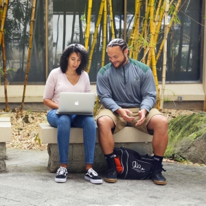 Two U H Manoa students sitting on a bench