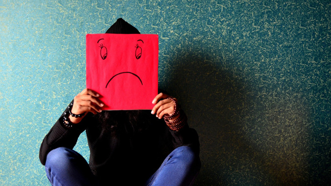Person holding a sad face sign