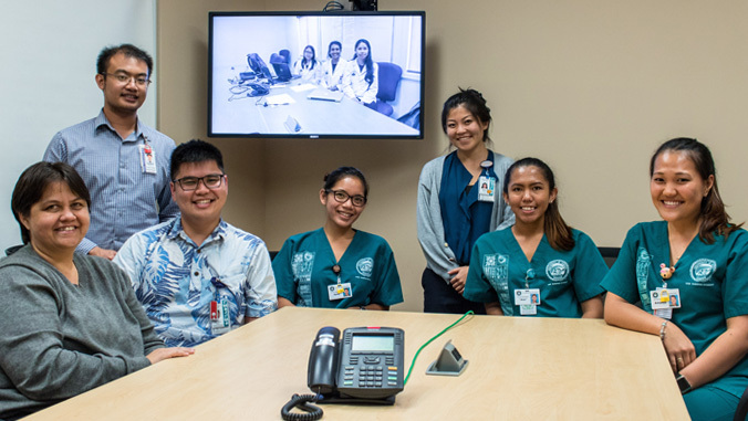 UH Mānoa and UH Hilo students on TV screen smiling