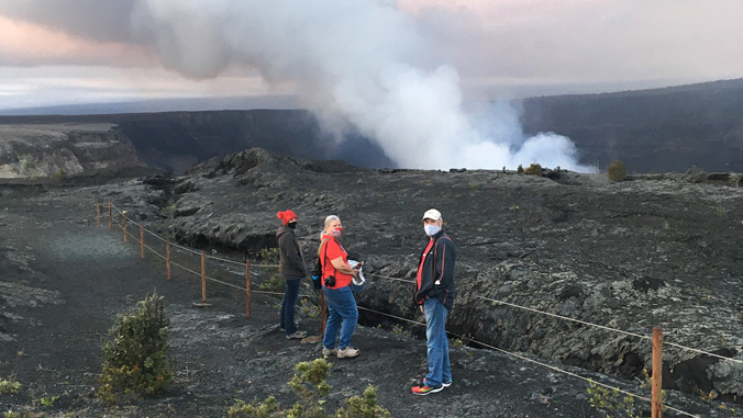 people watching plume from volcano