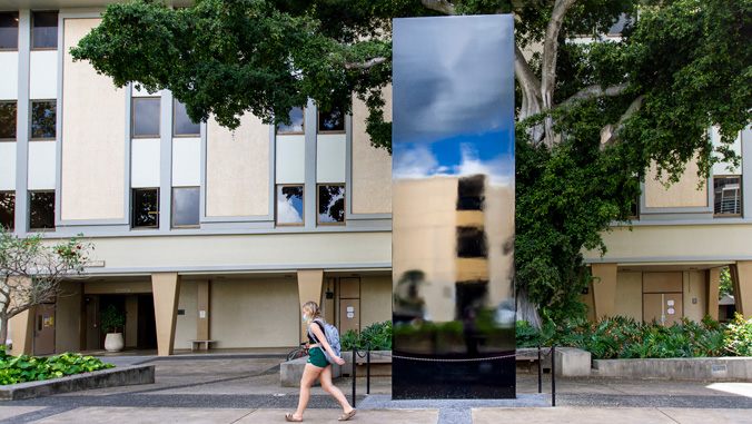 Student walking in front of the monolith