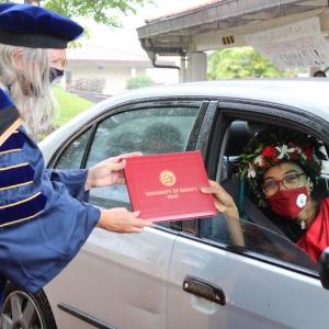 chancellor handing graduate a diploma in a car