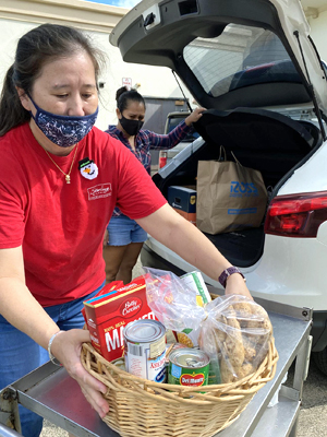 person loading food basket into back of car