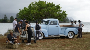 people standing around a blue truck