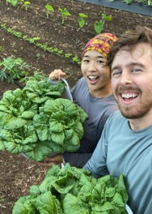 two people holding up their harvest and smiling
