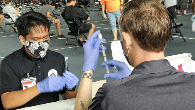2 people prepping syringes