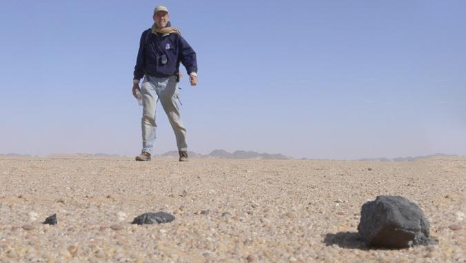 person looking at meteorite  - manoa fake news meteorite - THC in space? UH target of 'fake news' on social media