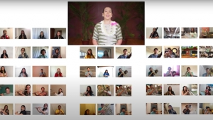 person singing on a zoom screen with dozens of other faces in boxes