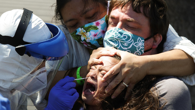 girl crying as worker swabs nose testing for COVID-19