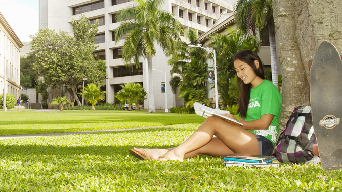 person sitting on grass looking at a book next to a tree