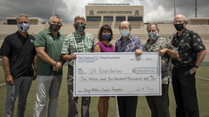 People holding check on Clarence T C Ching Field