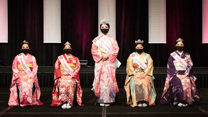 five people in kimono and face masks looking at the camera
