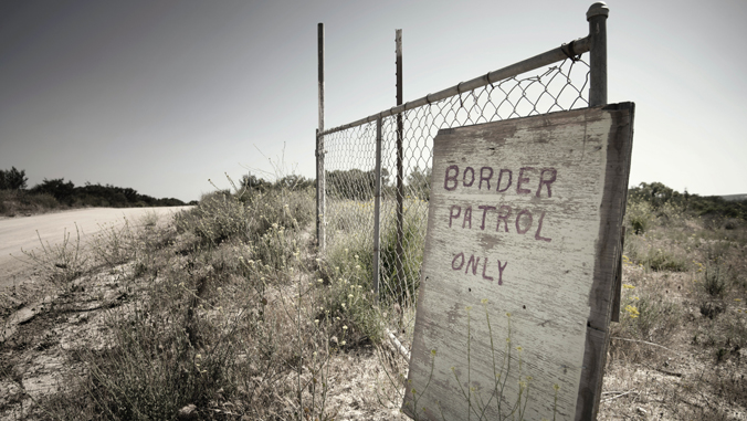 sign reading border patrol only leans against a fence in the desert